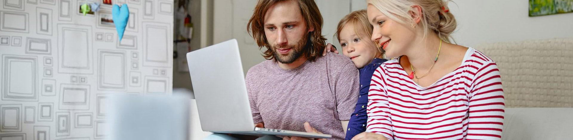 Ein Mann, eine Frau und ein Kind sitzen zusammen auf einem Sofa und blicken zusammen auf ein Notebook