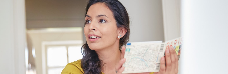 Assurance voyage - une dame tient un guide de voyage dans les mains